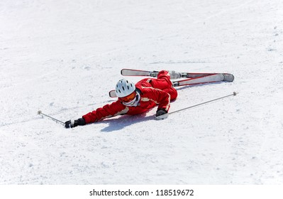 Female skier after falling down on a mountain slope