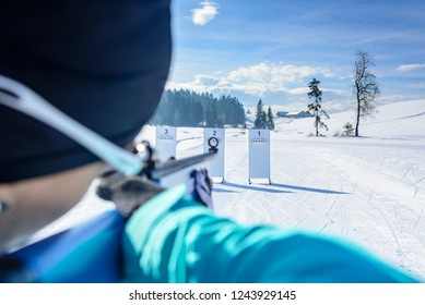 female skier doing biathlon shooting in standing position