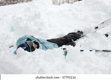 Female skier fallen into deep snow