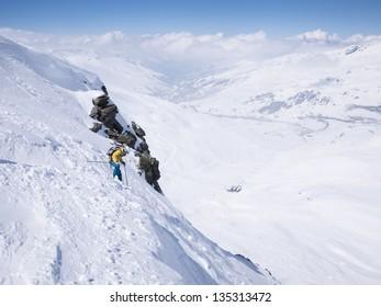 Female skier on steep slope above ski resort.
