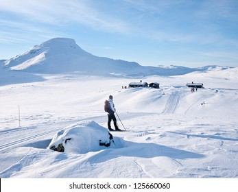 Female skier resting in a groomed ski track with a view towards a cluster of cabins in the norwegian mountains with a characteristic mountain summit in the background