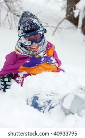 Female skier sitting in the deep snow, smiling