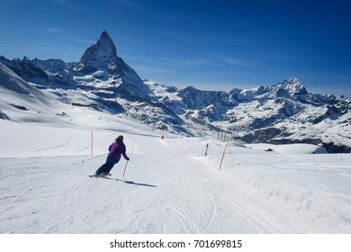 A female skier skiing without a helmet alone on the ski slope towards Matterhorn mountain on a beautiful sunny day with a thick layer of snow in ski resort Zermatt, canton of Valais in Switzerland.