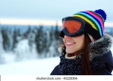 female skier smiling and wearing ski glasses in the mountains