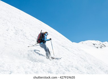 Female skier tackling a steep slope.