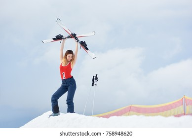 Female skier wearing ski pants and red bodice, standing on the top of the snowy hill with ski equipment. holding skis above a head at winter ski resort. Ski season and winter sports concept copyspace