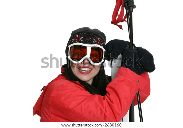 Female skier wearing warm red parka, beanie and goggles is leaning on skis and smiling.