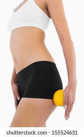 Female slender body with sport underwear holding orange on white background