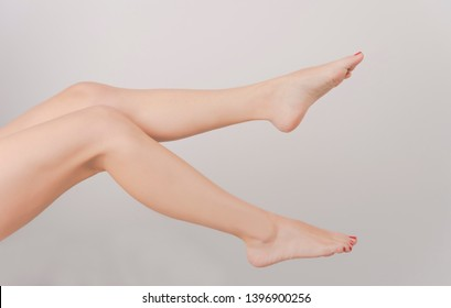 Female slim bare feet and beautiful legs, isolated on white background
