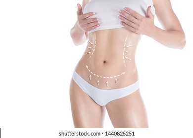 Female slim body in base underwear. Lifting marking with arrows in womans belly and waist, isolated on white. Selective focus. Plastic surgery, abdominoplasty, dieting, wellness, health, medicine