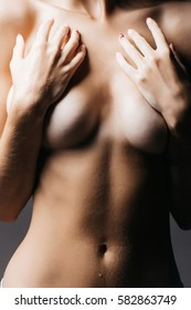 female slim body of young pretty sexy woman or girl topless with bare belly holding hands on chest or breast, closeup