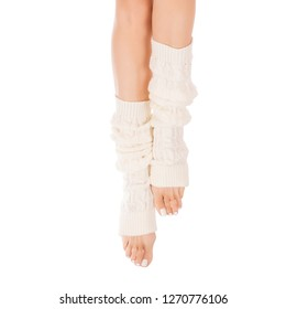Female slim legs in white leg warmers. White pedicure, close up, isolated on white background. Winter and hygge concept.
