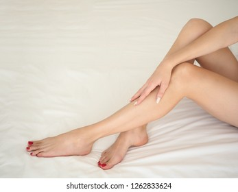Female slim long well groomed legs in bed, white bedding. Woman puts her hand on her beautiful calf. Body care, beauty and skin treatment concept.