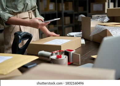 Female small business owner using mobile app on smartphone checking parcel box. Warehouse worker, seller holding phone scanning retail dropshipping package postal parcel bar code on cell technology.
