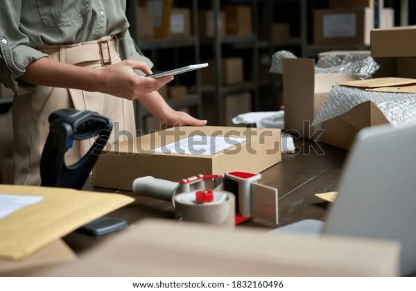 Mujer propietaria de una pequeña empresa que utiliza una aplicación móvil en la caja de cheques de smartphone. Empleado de almacén, vendedor que sostiene el escaneo del teléfono de la tienda de envío directo del paquete de envío directo código de barras de la tecnología celular.