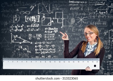 female smiling student with a big ruler pointing formulas on background