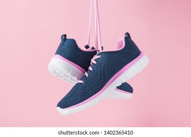 Female sneakers for run on pink background. Fashion stylish sport shoes, close up