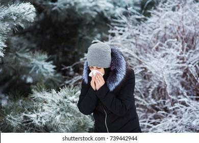 Female sneezing. Pretty young woman has flu and fever in winter day outdoor.