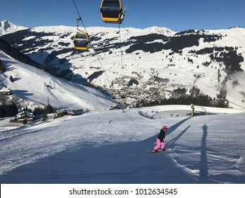 female snowboarder boarding over the piste with view downwards into the valley of Saalbach-Hinterglemm in Austria