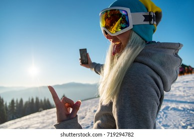 Female snowboarder enjoying sunset after snowboarding, using her smart phone, taking pictures of winter nature in the mountains copyspace connectivity mobility freeride lifestyle concept