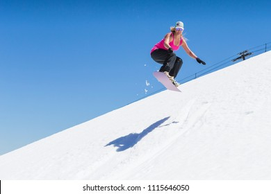Female snowboarder jumping off lip in spring weather.  She is wearing a pink tank top and hat.