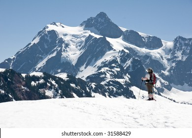 A female snowshoer pauses for a commanding view of Mt. Shuksan