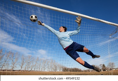 A female soccer player diving to catch the ball