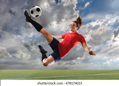 Female soccer player kicking ball outdoors