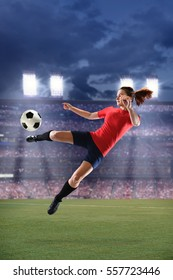 Female soccer player kicking ball during match inside large stadium
