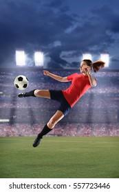 Female soccer player kicking ball during match inside large stadium