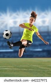 Female soccer player kicking ball in large stadium