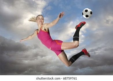 Female soccer player kicking a ball in midair.