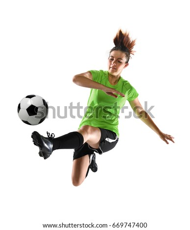 Female soccer player kicking ball isolated over white background