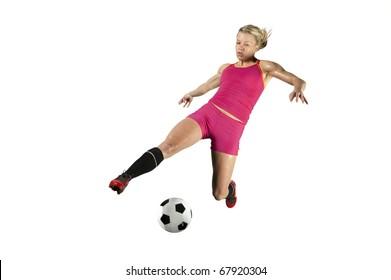 Female soccer player kicks a ball in mid air.