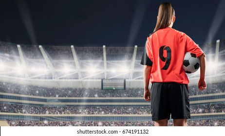 female soccer player standing with the ball against the crowded stadium at night