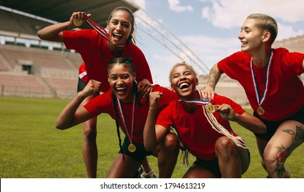 Female soccer players cheering together after the game league. Football team with medals screaming together after winning the competition.