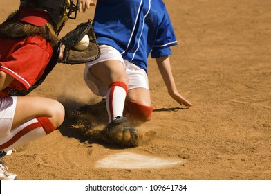 Female softball player sliding into base with baseman in the foreground