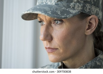 A female soldier looking out a window, blank stare