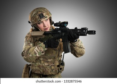 Female soldier in tactical uniform with rifle. Shot in studio. Isolated with clipping path on grey background
