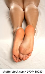 female soles on a white bed and white background