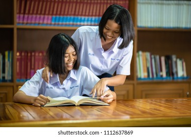 Female southeast Asian high school students are studying in the library.