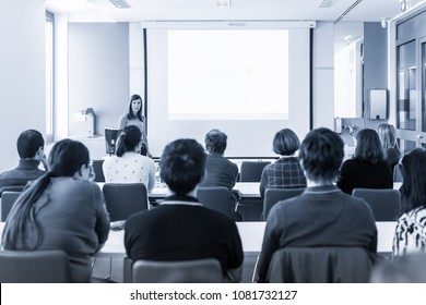 Female speaker giving presentation in lecture hall at university workshop. Rear view of unrecognized participant in audience. Scientific conference event. Black and white blue toned image.
