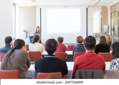 Female speaker giving presentation in lecture hall at university workshop. Audience in conference room. Rear view of unrecognized participant in audience. Scientific conference event.