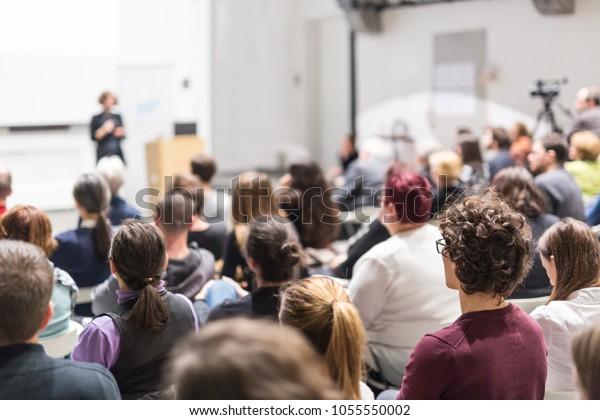 Une conférencière présente dans une salle de conférence à l'atelier universitaire. Le public dans la salle de conférence. Vue arrière d'un participant non reconnu dans le public. Conférence scientifique.