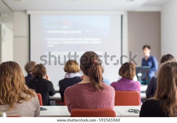 Vorträge von weiblichen Referenten in der Vorlesungshalle der Universität. Hintere Ansicht von nicht anerkannten Teilnehmern, die Vorträge hören und Notizen machen. Wissenschaftliche Konferenz.