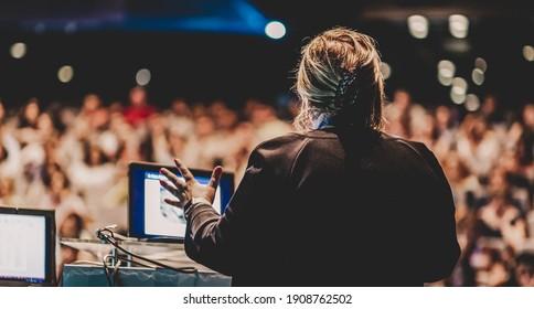"""Muttersprachlerin, die einen Vortrag über Unternehmenskonferenzen hält. Unerkennbare Menschen im Publikum im Konferenzsaal. Veranstaltung """"Unternehmen und Unternehmertum""""."""