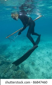 Female spear-fisher reloads spear-gun at surface of water