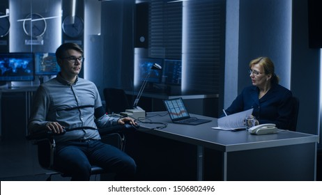 Female Special Agent Conducts Lie Detector / Polygraph Test on a Young Suspect. Expert Examiner Questions Accused in Interrogation Room Writes Down Reactions.