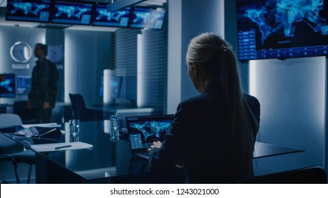 Female Special Agent Works on a Laptop in the Background Special Agent in Charge Talks To a Military Man in the Monitoring Room. Background Busy System Control Center with Monitors Showing Data Flow.