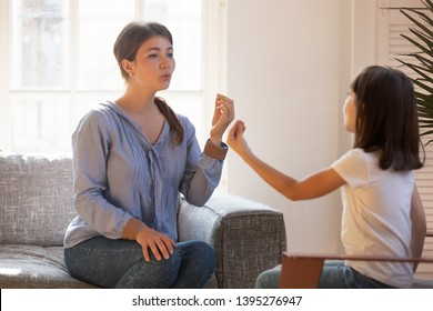 Female speech therapist doing exercise, speaking with little girl patient, stuttering child studying with doctor at home, repeat sounds and words, training articulation and pronunciation
